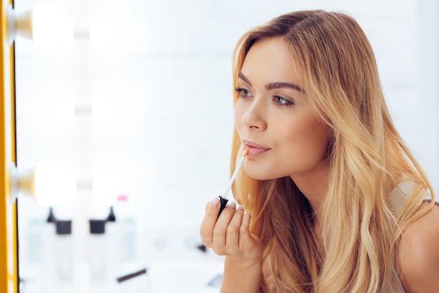 Voeg wat glans toe aan haar look. zijaanzicht van een mooie jonge vrouw die lippenstift aanbrengt en naar haar spiegelbeeld kijkt terwijl ze aan de kaptafel zit
