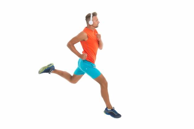 Voel het ritme. motiverend lied. man sportman loopt met koptelefoon. runner knappe sterke kerel beweging geïsoleerd op wit. muziek voor training. loop sneller. hardloopsport. blijf rennen.