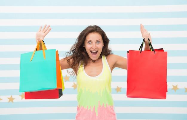 Voel je vrij om alles te kopen wat je wilt. vrouw draagt bos boodschappentassen gestreepte achtergrond. eindelijk favoriete merk gekocht. tips winkelverkoop. meisje tevreden met winkelen. voordelige aankoop zwarte vrijdag.