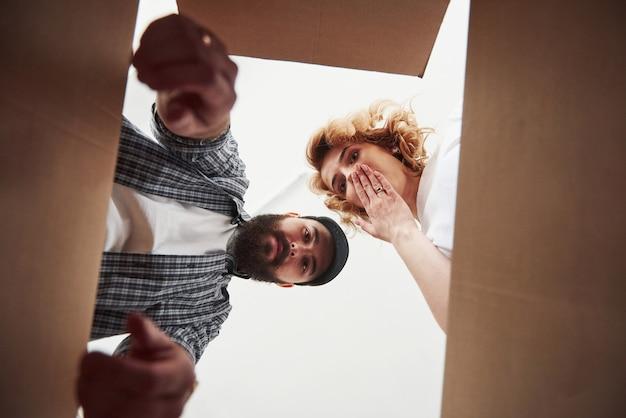 Voelt zich geschokt. gelukkig paar samen in hun nieuwe huis. conceptie van verhuizen