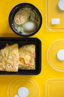 Voer de hele dag in bakjes op een gele ondergrond. dieet voor ontbijt, lunch en diner. juiste voeding en gewichtsverlies. dieetplanning