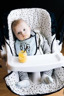 Voeren. aanbiddelijk babykind dat met een lepel als hoge voorzitter eet. baby