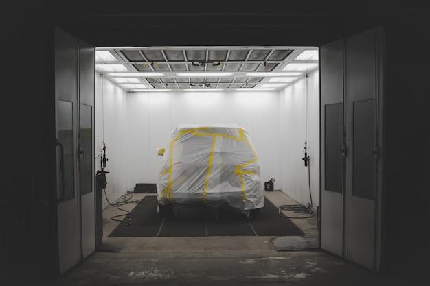 Voertuig bedekt met een wit vel en gele tape in een garage voor autoservice