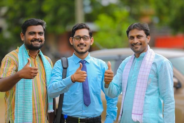 Voertuig lening concept: jonge indiase bankier en boeren staan met nieuwe auto en laten zien.