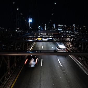 Voertuigen op brug bij nacht met motieonduidelijk beeld