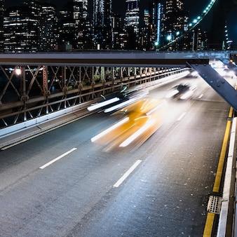 Voertuigen op brug met motion blur 's nachts