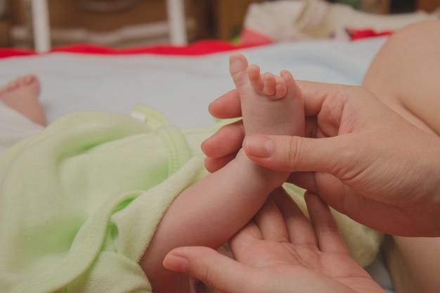 Voet de slapende baby in de handen van moeder