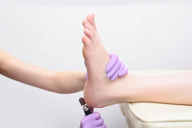 Voet huid behandelingsproces. gehandschoende handen met een pedicuremachine. detailopname