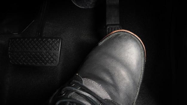 Voet indrukken voetpedaal van een auto om te rijden. gaspedaal en rempedaal in een auto. bestuurder die de auto bestuurt door het gaspedaal in te drukken en de pedalen van de auto te breken. binnen voertuig. bedieningspedaal. detailopname.