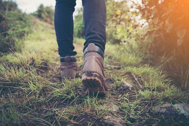 Voet van de vrouw reiziger met rugzak ontspannen buiten met rotsachtige bergen op de achtergrond zomervakanties en lifestyle wandelen concept.