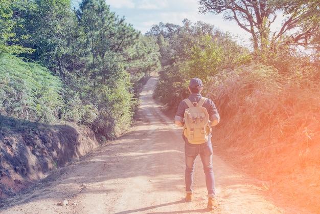 Voet van jonge man reiziger met rugzak ontspannen buiten met rotsachtige bergen op achtergrond zomervakanties en lifestyle wandelen concept.