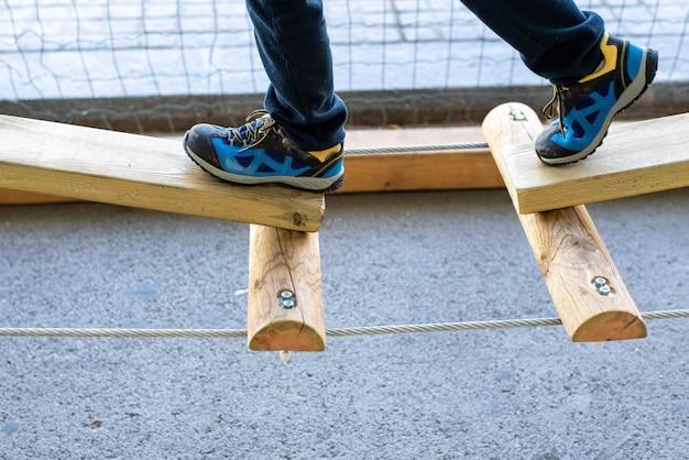 Voet van kind die saldi op houten raad in een stedelijk avonturenpark doen.
