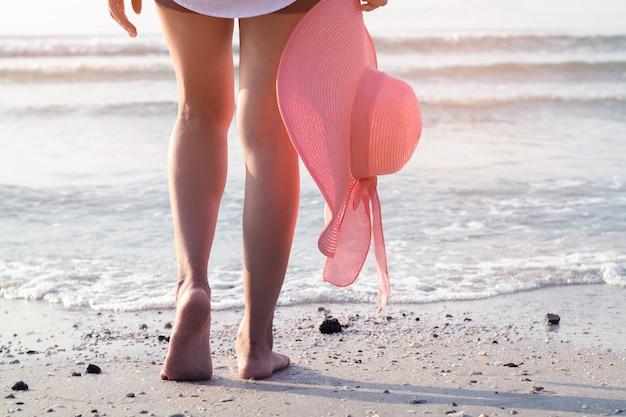 Voet van vrouw die op het strand met het houden van roze hoed loopt