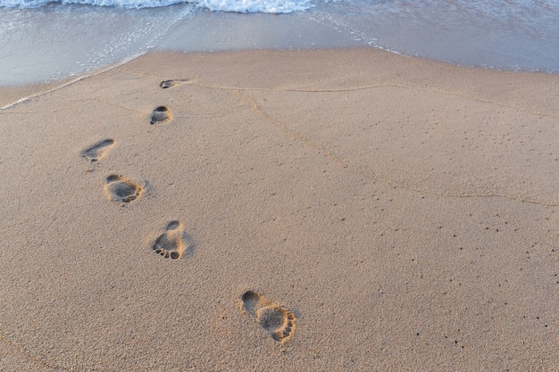 Voetafdruk in het zand op de achtergrond van het strand