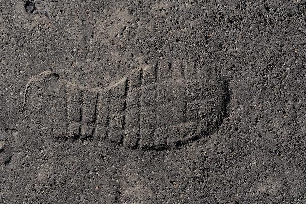 Voetafdruk in zwart zand op de achtergrond van ijsland