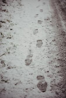 Voetafdrukken in besneeuwde weg