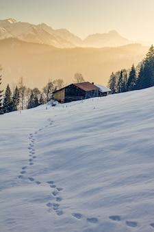 Voetafdrukken in sneeuw naar houten hut in bergen van allgau