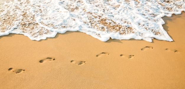 Voetafdrukken op een helder zandstrand en een schone witte golf