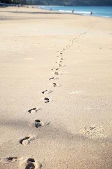 Voetafdrukken op het lichte zand van het zeestrand op een zonnige dag