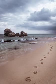 Voetafdrukken op het strand aan de oceaankust