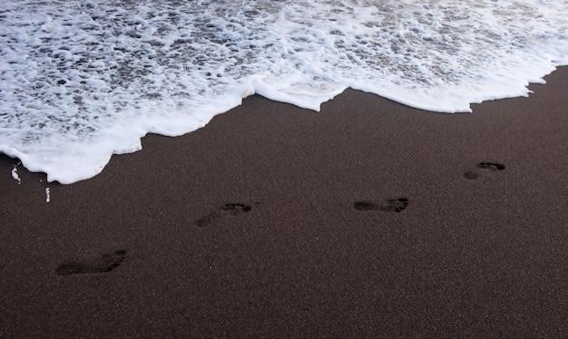 Voetafdrukken op het strand tijdens zonsondergang in de zomer
