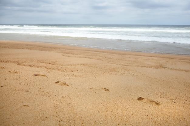 Voetafdrukken op het zand bij de golven van het strand