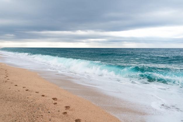 Voetafdrukken op het zand op het lege strand