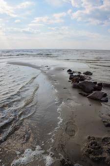 Voetafdrukken op nat zand bij een stapel stenen aan de kust met een branding tegen een bewolkte hemel