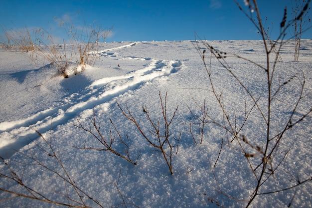 Voetafdrukken op sneeuwbanken na wandelen, bevriezen en winterse sneeuwval