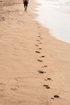 Voetafdrukken van een man lopen op het strand. reis concept