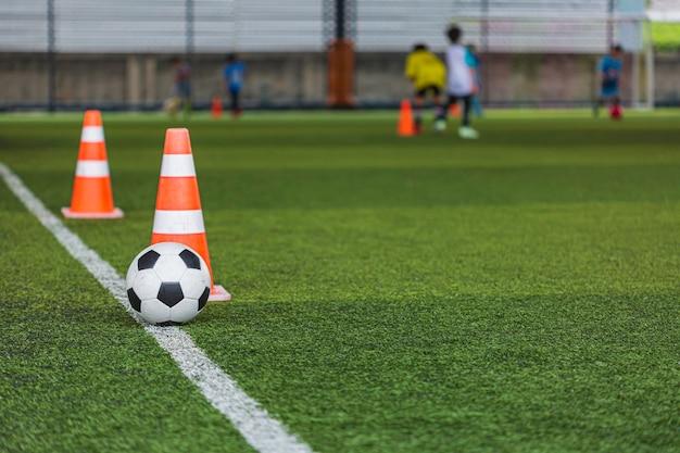 Voetbal bal tactiek kegel op grasveld met voor opleiding achtergrond kinderen trainen in voetbal