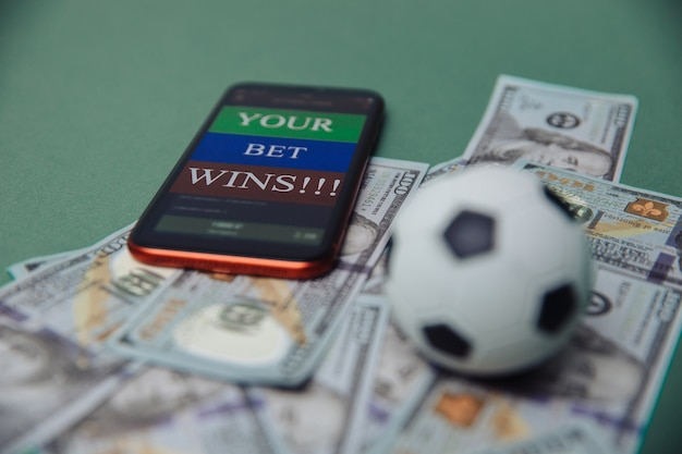 Voetbal bedrijfsconcept. bal en smartphone met wedtoepassing op dollarbiljetten en groene achtergrond. voetbal gokken geld concept.