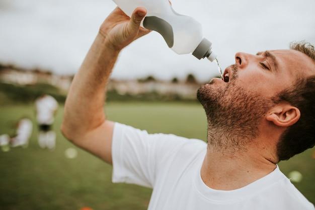 Voetbal coach drinkwater na voetbalwedstrijd
