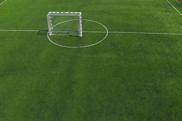 Voetbal doel in het midden van een voetbalveld op groen gras.