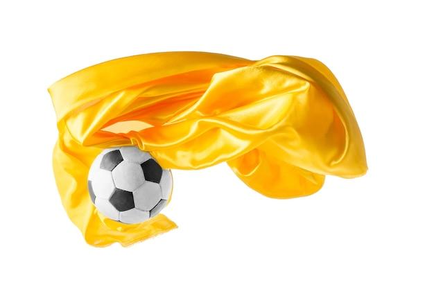 Voetbal en gladde elegante transparante gele doek geïsoleerd of gescheiden op witte studio achtergrond.