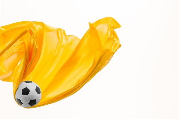 Voetbal en gladde elegante transparante gele doek geïsoleerd of gescheiden