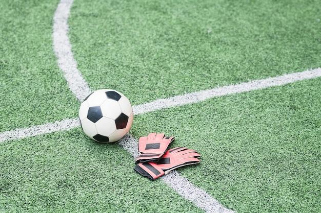 Voetbal en lederen handschoenen van voetballer op gekruiste witte lijnen van groen leeg veld voor trainingen en wedstrijden