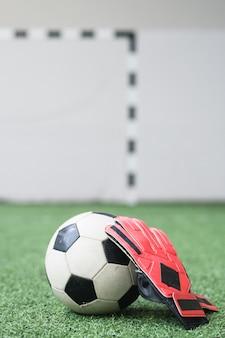 Voetbal en lederen handschoenen van voetballer op groen leeg veld voor sporttrainingen en wedstrijden