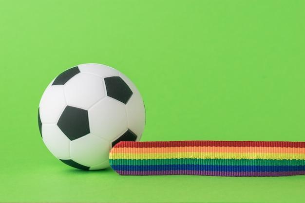 Voetbal en lgbt-tape op een groene achtergrond. het concept van lgbt in het voetbal.
