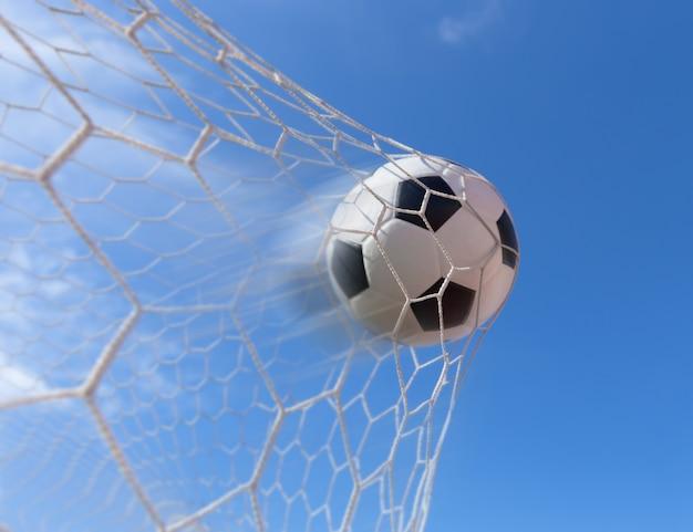 Voetbal in doel met blauwe hemel