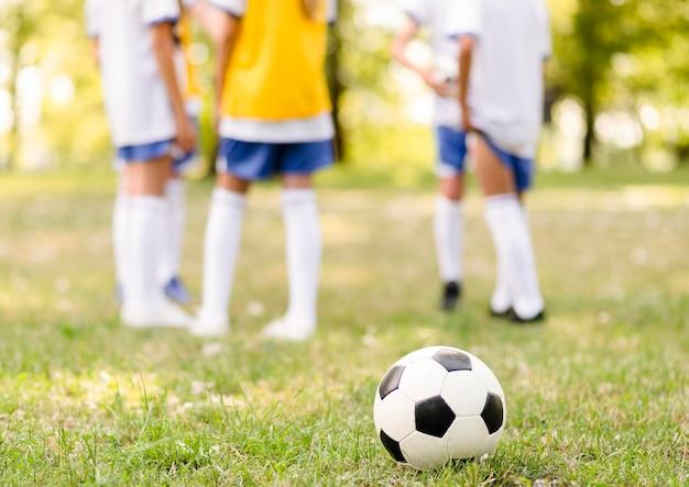 Voetbal in gras naast kinderen