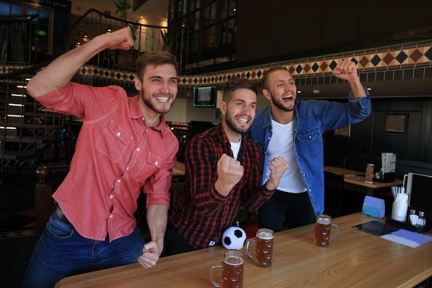 Voetbal kijken in de bar. gelukkige vrienden die bier drinken en juichen voor het favoriete team, de overwinning vieren.