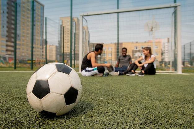 Voetbal liggend op het veld of de speelplaats van drie jonge spelers die pauze hebben na de training