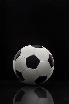 Voetbal met reflectie op de tafel op een donkere muur