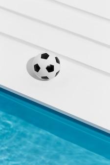 Voetbal naast zwembad