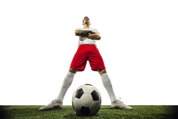 Voetbal of voetballer op witte muur met gras. jonge mannelijke sportieve modeltraining. aanvallen, vangen. concept van sport, competitie, winnen, actie, beweging, overwinnen. wijde hoek.