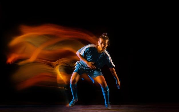 Voetbal of voetballer op zwarte studio