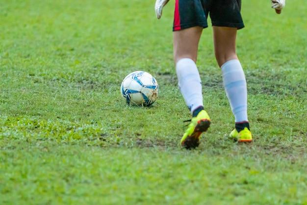 Voetbal of voetbalster ongeveer om de voetbal op grasgebied te schoppen