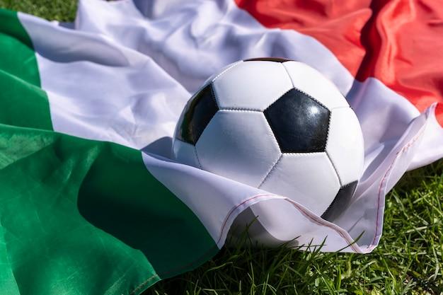 Voetbal op achtergrond van italiaanse vlag wapperen in de wind op groen gras europese kampioenen