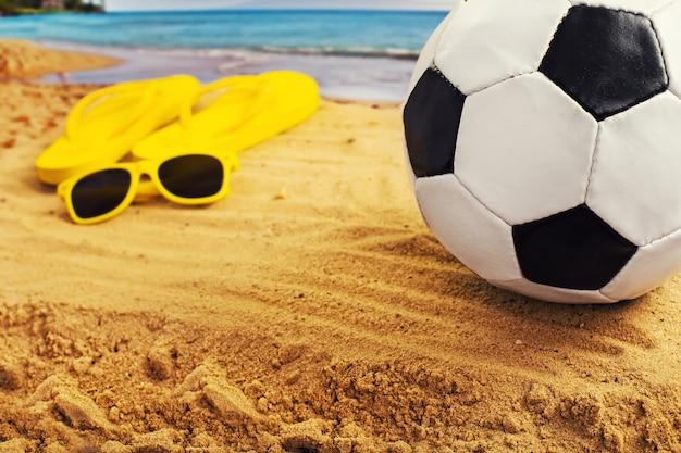 Voetbal op het zand met flip flop schoenen op het strand